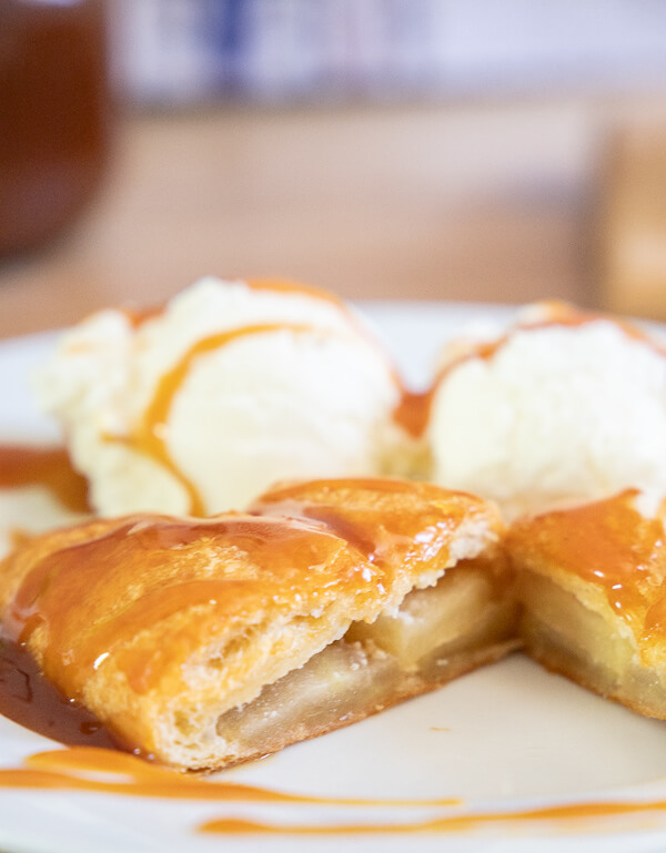 This is a great sweet treat to make for your family! With spiced apples, sweet cheesecake filling all wrapped up in crescent rolls! Top it with my favorite homemade caramel sauce recipe and some vanilla ice cream and you have the most decadent dessert in no time!