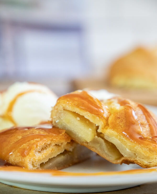 Sweet apple dessert with indulgent cream cheese and homemade caramel sauce wrapped in a crescent roll!