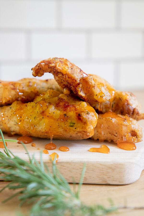 The crispiest fried chicken recipe ever! It has a flavorful herb infused batter and its topped off with a honey Sriracha sauce that is sweet and spicy!