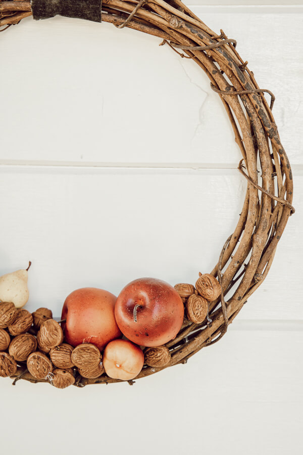 How to make a stylish DIY wreath for fall with faux apples and walnuts! These are so easy to make and cost less than store bought wreaths.