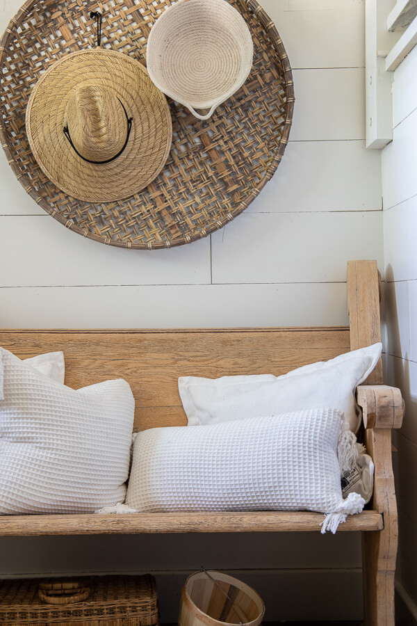 Fall decor ideas including my wooden church pew in the entry with baskets on the wall, topped with straw hats and rope baskets.  White pillows top of the vintage church pew and a basket of pears adds a touch of color to this neutral fall entryway.