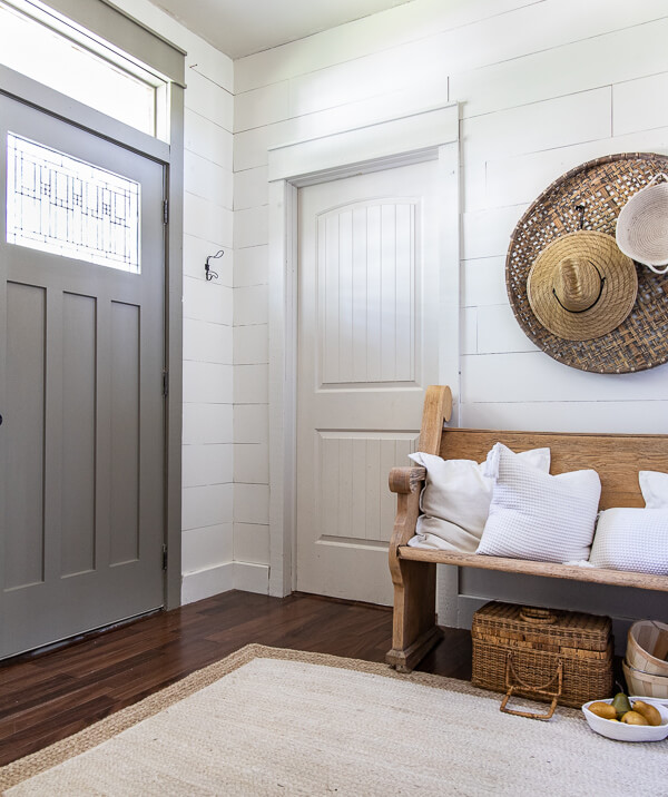 Door painted with Benjamin Moore Gettysburg Grey.  Fall decor ideas including my wooden church pew in the entry with baskets on the wall, topped with straw hats and rope baskets.  White pillows top of the vintage church pew and a basket of pears adds a touch of color to this neutral fall entryway.