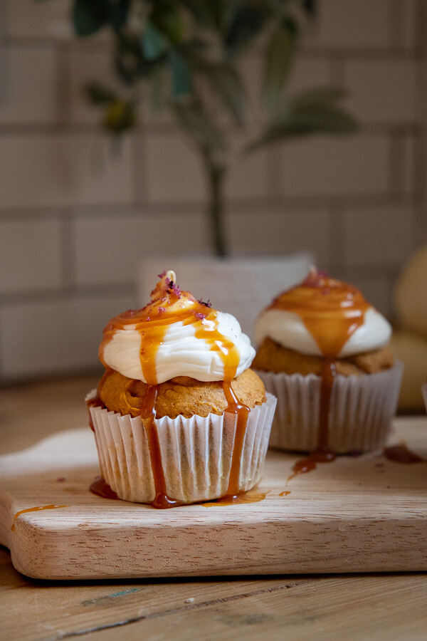 Utterly decadent fall inspired pumpkin cupcakes topped with cream cheese frosting, caramel and sea salt. It has all the flavors of fall!