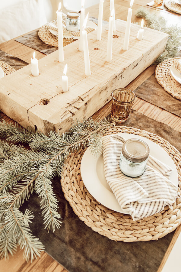 Love these mason jar Christmas tree scenes on this gorgeous Christmas tablescape with candles.