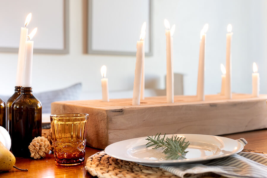 A unique wood candle holder, amber drinking glasses, striped napkins, and simple white dishes create a wonderfully cozy and intimate Thanksgiving tablescape.  Thanksgiving table decor can be simple and inexpensive and still make an impact!