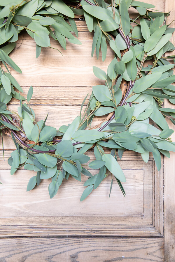 How to make a faux eucalyptus wreath with 3 items, and in less than 5 minutes! Its also easily changeable using floral wire, you can change this wreath out seasonally and make it over as often as you want!