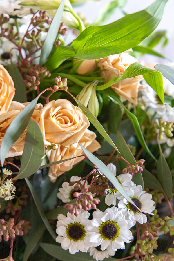Peach roses, seeded eucalyptus, miniature lilies, and adorable tiny white daisies make a gorgeous and relaxed springtime floral arrangement.
