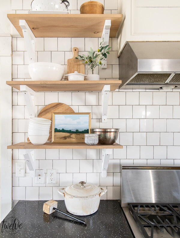 Open shelves in the kitchen with cutting boards, gorgeous white dishes, copper bowls, and custom landscape art that you can get yourself! This landscape art is available for FREE, click here to get your own FREE printable art!