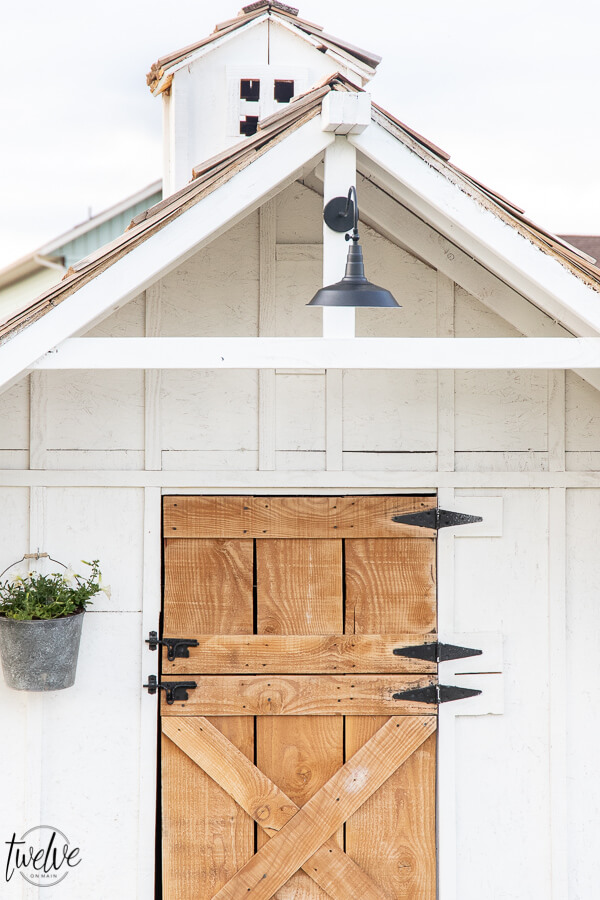 Check out this amazing simple and stylish white and rustic goat house! Looking for goat shed ideas? We combined function, along with a rustic dutch door, a stylish solar light, rustic shake roof, white board and batten, and so much more to create a simple but stylish goat house!