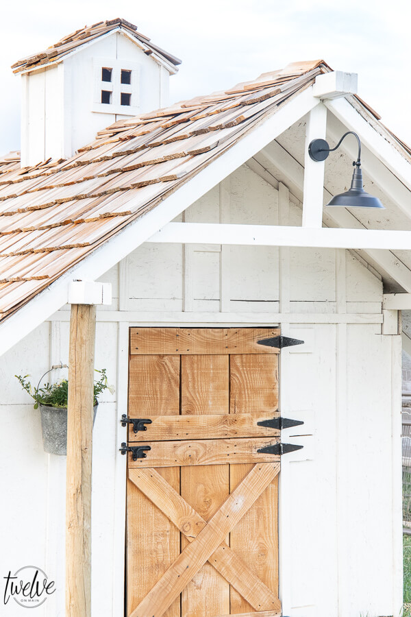 Check out this amazing simple and stylish white and rustic goat house! Looking for goat shed ideas? We combined function, along with a rustic dutch door, a stylish solar light, rustic shake roof, white board and batten, and so much more to create a simple but stylish goat house! Also includes a gorgeous cupola on the top of the roof!
