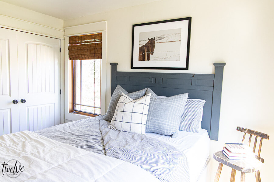 Teenage boys bedroom complete with simple white walls using Benjamin Moore Dove White, ticking strip bedding, grey plaid pillows and some horse photography to round it out.