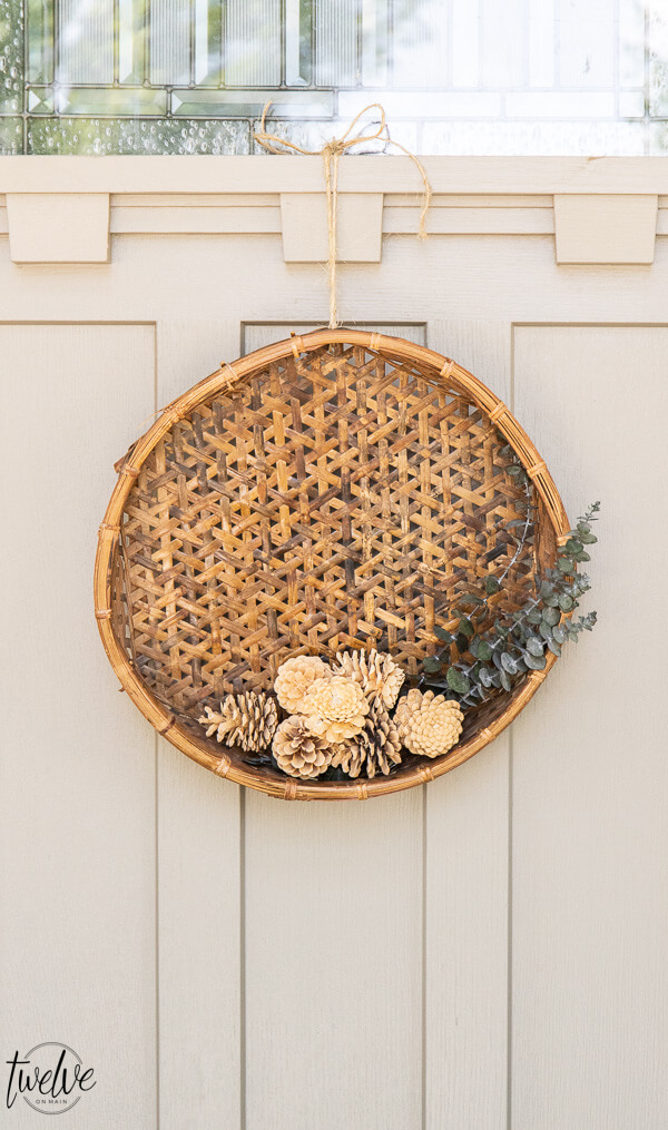 Fall wreath with eucalyptus, pine cones and a rustic basket give all the gorgeous earthy tones perfect for the autumn weather.