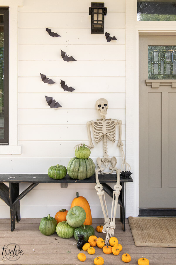 Affordable Halloween porch ideas including paper bats, real pumpkins, and a spooky posable skeleton!