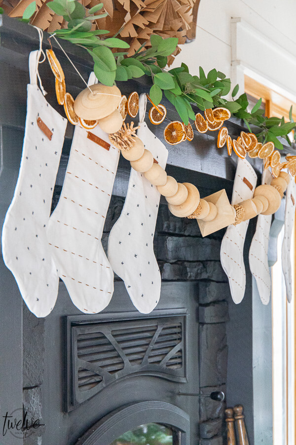 Gorgeous boho/Scandinavian holiday mantel complete with eucalyptus, dried orange slices, and wooden bead garland.