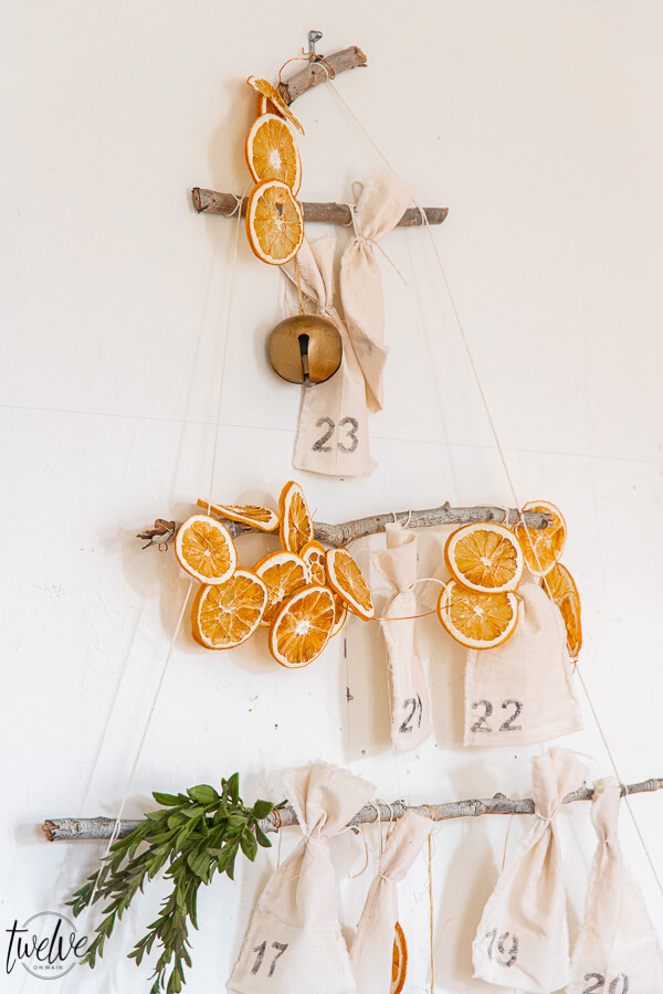 How to create a gorgeous and fun advent calendar DIY!  This Christmas tree advent calendar uses tree branches and dried oranges!   It is a fun interactive advent calendar, but it is also gorgeous and can be used as a focal point of your Christmas decor!