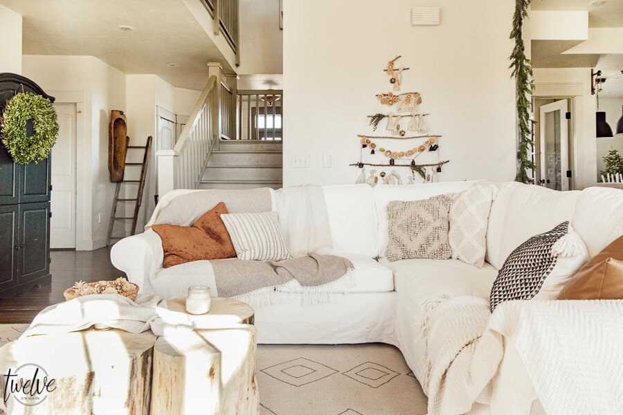 Get some cozy Christmas living room decor inspiration with wood stump coffee tables, cedar garland, a unique advent calendar, white Ektorp sectional, gorgeous painted black fireplace and so much more.