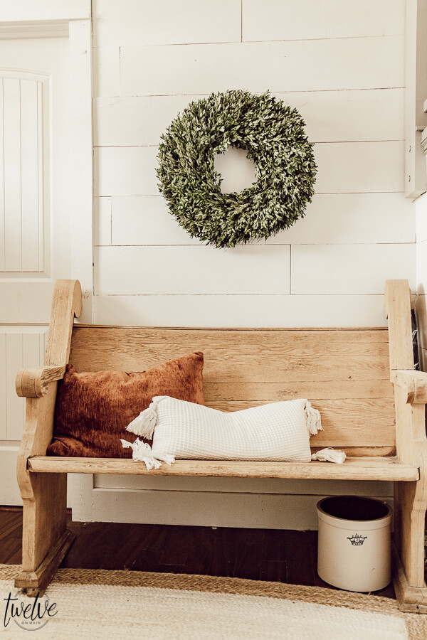 Simple winter decor in the entryway using a festive boxwood wreath and a warm rust colored pillow.