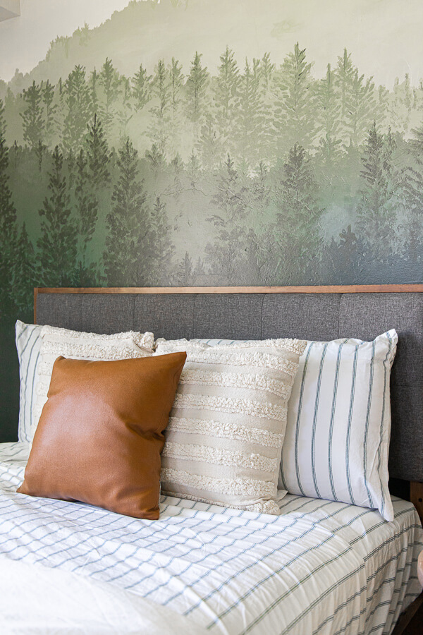 Gorgeous guest bedroom complete with a cozy bed, beautifully painted custom forest wall mural, cozy seating, and so much more.